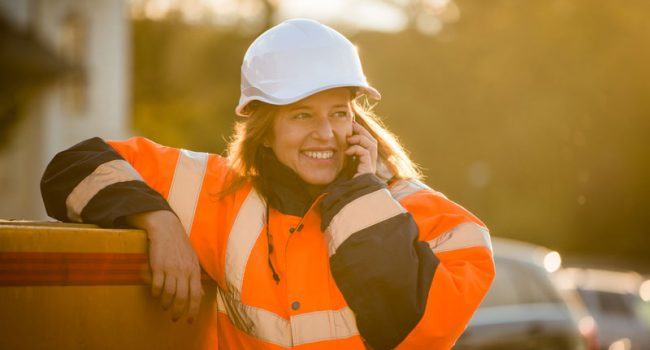 women wearing hard hat talking on the phone